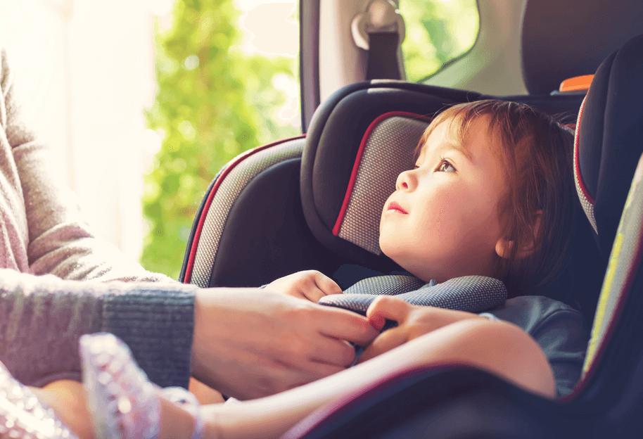 Gambar ini menunjukkan sebuah anak duduk pada Car Seat di dalam Mobil dan terlihat 2 tangan sedang memegang sabuknya