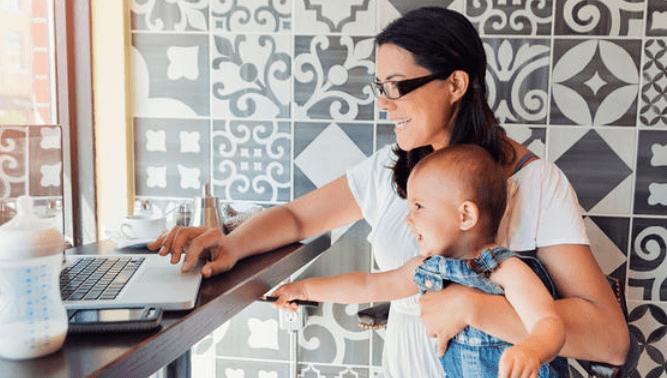Gambar ini menunjukkan seorang prempuan sedang memangku seorang bayi dan melihat ke laptop