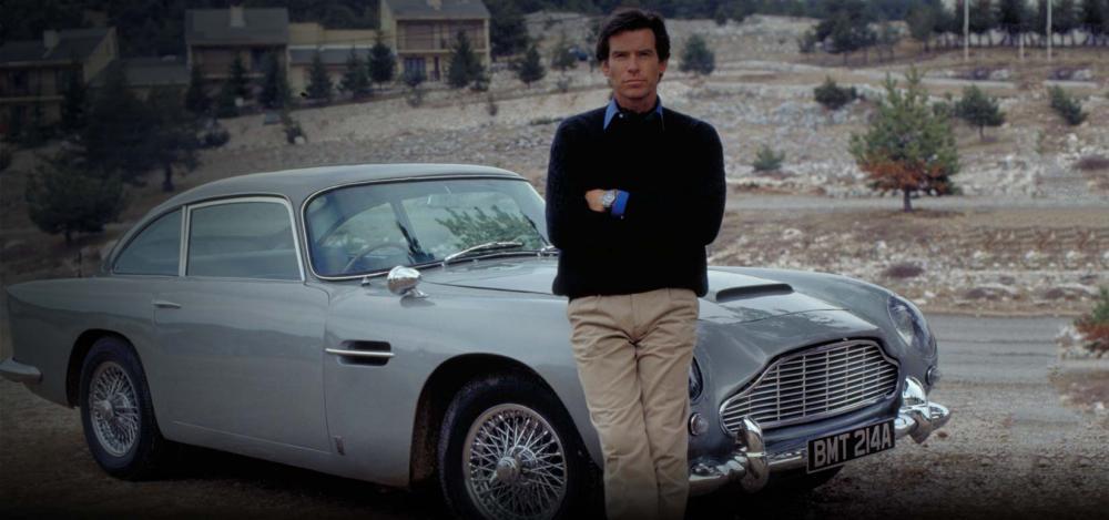 Gambar yang menunjukan seorang Pierce Brosnan yang berpose bersama Aston Martin DB5