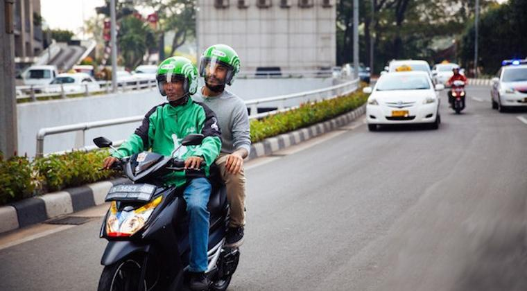 Gambar yang menunjukan driver ojek online yang sedang membonceng penumpang