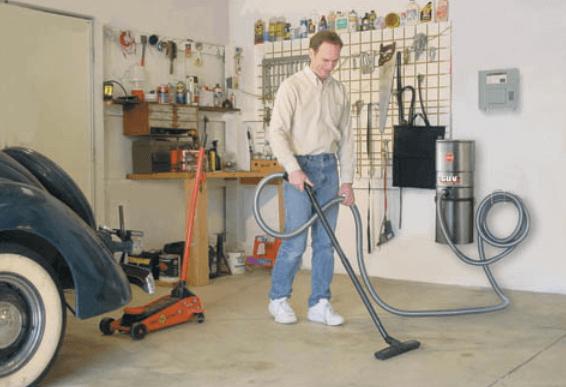 Gambar ini menunjukkan seorang pria memegang vacum cleaner sedang membersihkan garasi