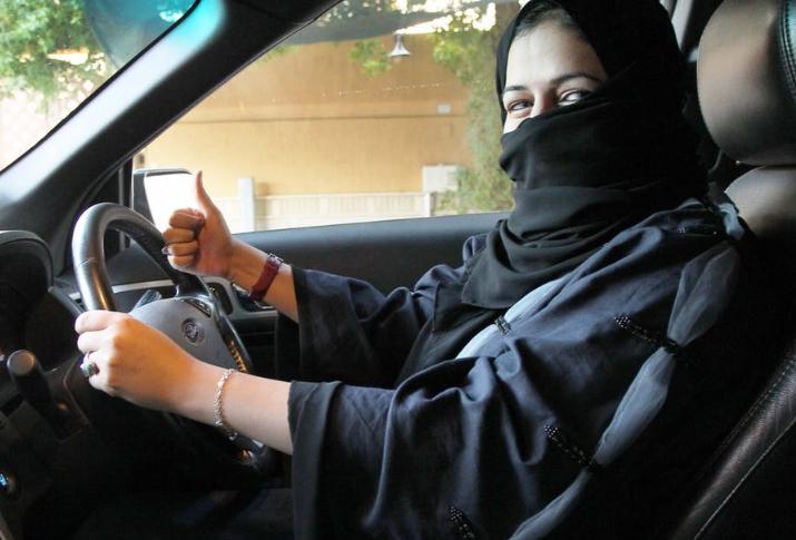 Gambar ini menunjukkan seorang perempuan memegang kemudi Mobil dan mengacungkan jempolnya