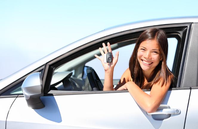 Gambar ini menunjukkan seorang wanita sedang berada di dalam Mobil dan menunjukkan kuncinya