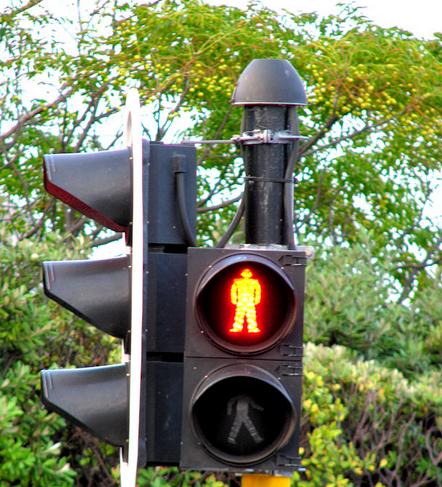 Gambar ini menunjukkan lampu lalu lintas di pinggir jalan dengan lampu warna kuning gambar orang menyala