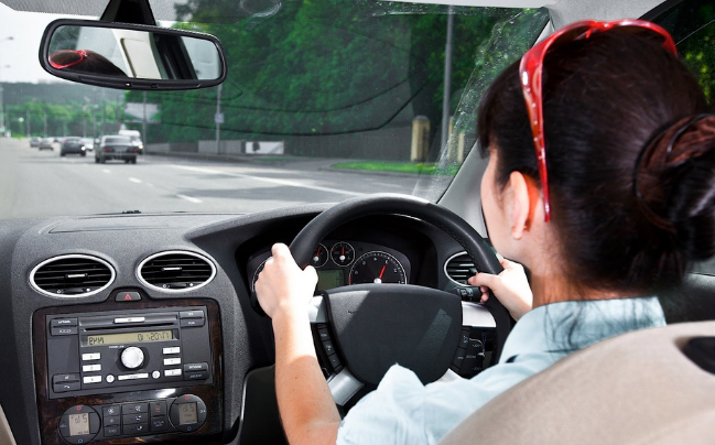 Gambar ini menunjukkan seorang wanita tampak belakang sedang mengamudi Mobil dan terlihat beberapa Mobil