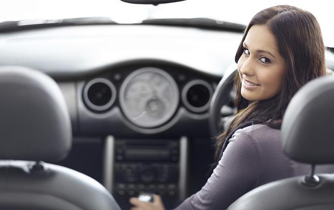 Gambar ini menunjukkan seorang wanita dengan berkendara dalam Mobil dan menghadap belakang