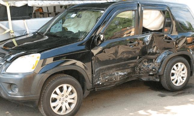 Gambar ini menunjukkan sebuah Mobil warna hitam penyeok bekas ditabrak dari samping