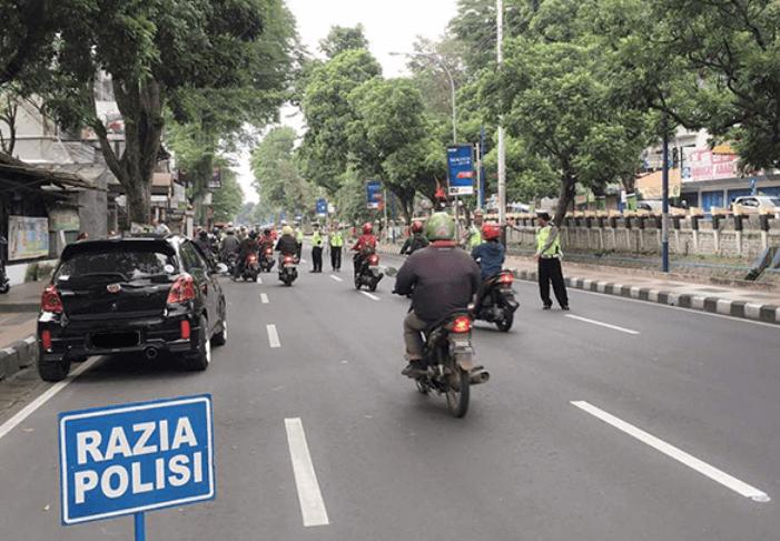 Gambar ini menunjukkan tanda adanya pemeriksaan kelengkapan surat bertuliskan Razia Polisi dan terdapat banyak pengendara dan polisi di jalan