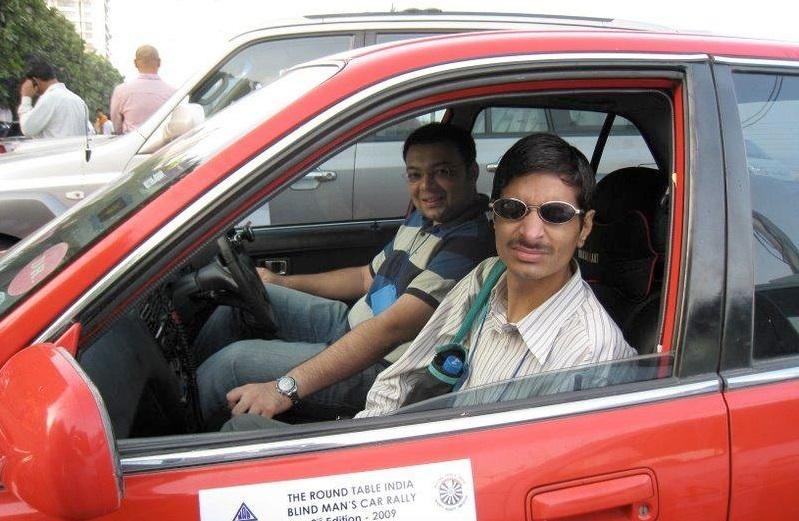 Gambar yang menunjukan seorang tuna netra yang sedang berfoto di dalam mobil