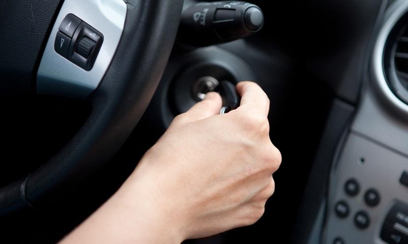 Gambar yang memperlihatkan seseorang yang sedang menghidupkan mobil