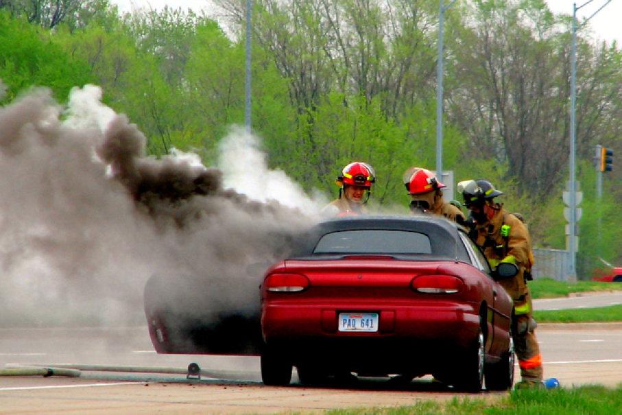 Gambar yang menunjukan petugas pemadam kebakaran memadamkan asap pada mobil