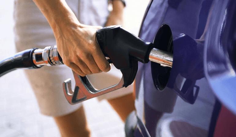 Gambar Ini menunjukkan sebuah tangan memegang alat pengisi bahan bakar dimasukkan ke lubang tangki Mobil