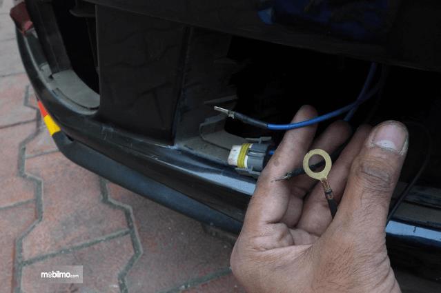 Gambar ini menunjukkan sebuah tangan sedang memegan beberapa kabel  yang terdapat pada bagian depan kendaraan