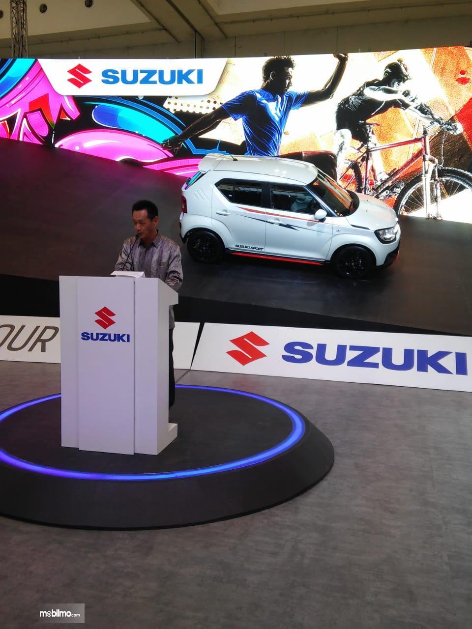 gambar menunjukan seorang mempresentasi di booth Suzuki GIIAS 2018
