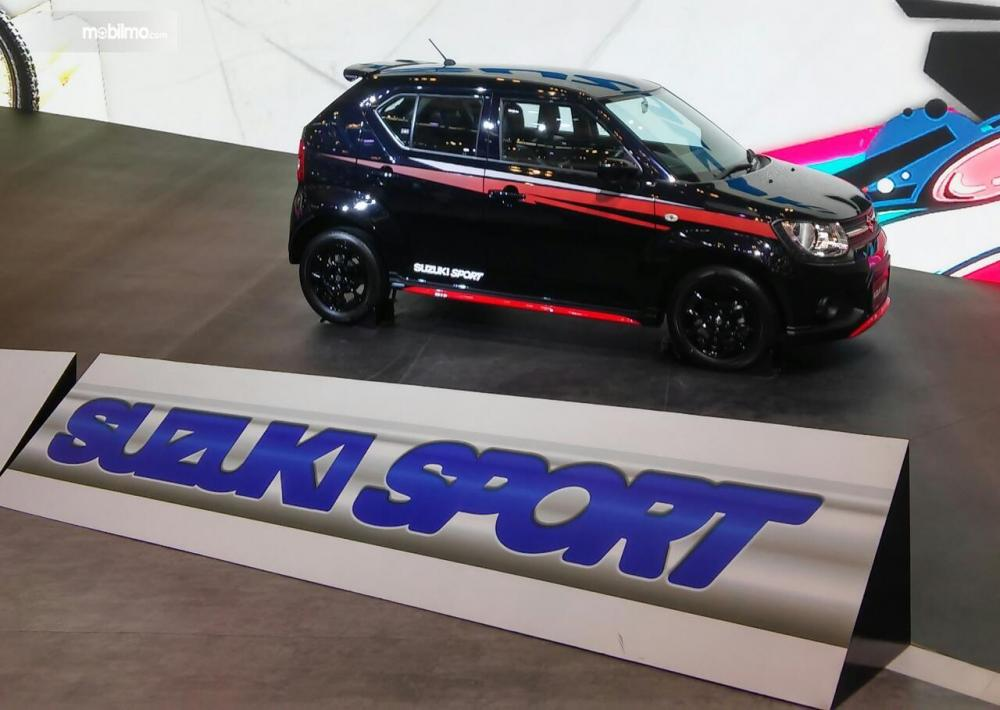 gambar menunjukan sebuah mobil Suzuki Sport berwarna hitam di booth Suzuki