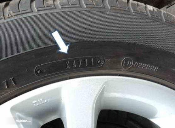 Gambar ini menunjukkan dinding ban Mobil dengan velg warna putih dan terdapat tanda panah menunjuk kode ban