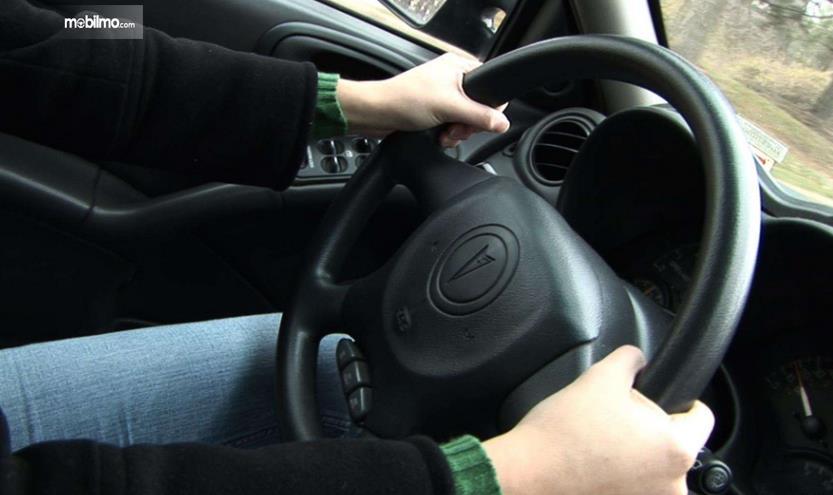 Gambar ini menunjukkan 2 buah tangan memegang kemudi Mobil dengan posisi jam 9 dan jam 3