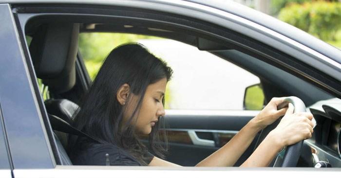 Gambar yang menunjukan seorang wanita yang sedang tertidur ketika menyetir