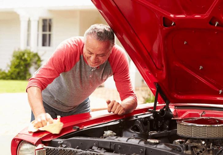 Gambar ini menunjukkan seorang pria sedang memeriksa mesin Mobil warna merah
