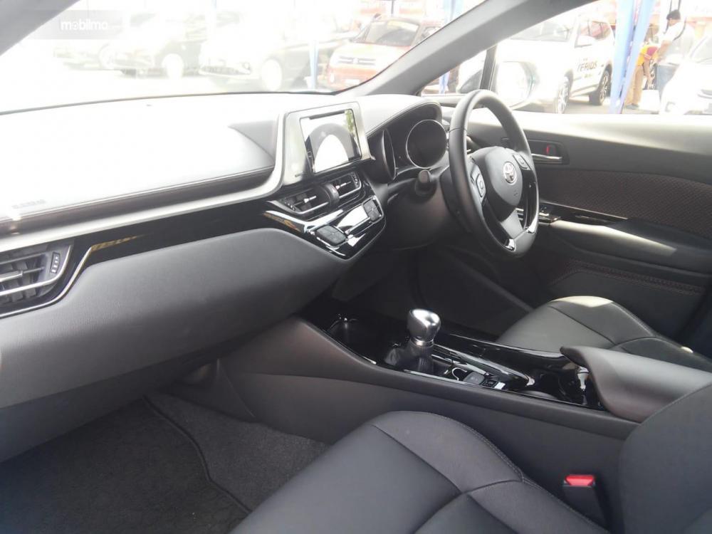dashboard dan setir Toyota C-HR 2018 dengan head unit dan kontrol ac yang didesain simetris