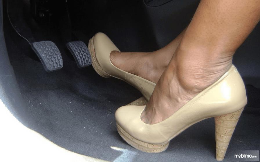 Gambar ini menunjukkan 2 kaki memakai sepatu hak warna cokelat dan yang kanan menekan pedal gas