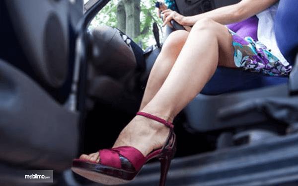 Gambar ini menunjukkan seorang wanita berada di kursi pengemudi dengan memakai sepatu hak warna merah
