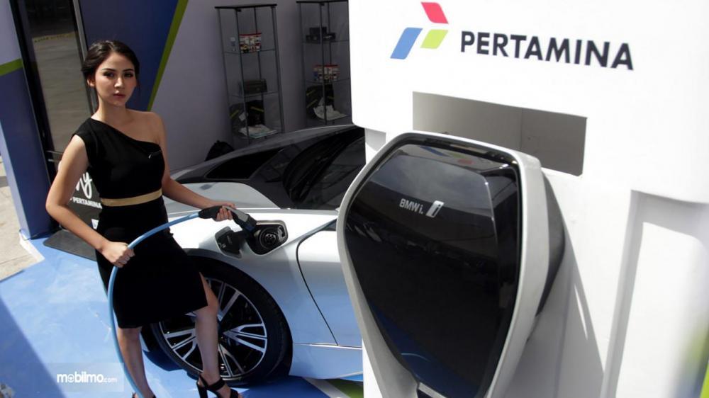 SPG tunjukkan cara penggunaan dispenser pengisian mobil listrik