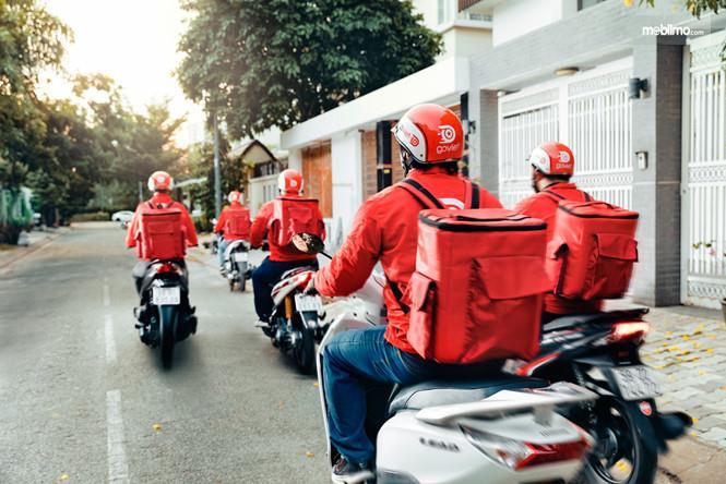 Gambar yang menunjukan Go-Viet yang sedang mengendarai motor dan berbaju merah