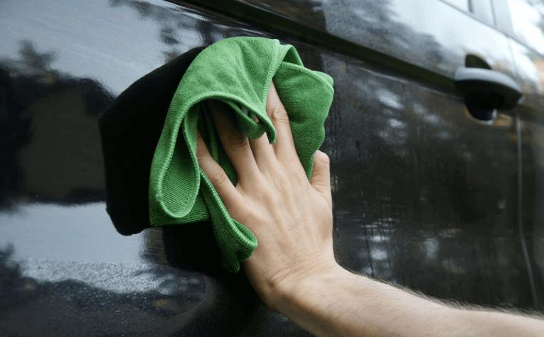 Gambar ini menunjukkan sebuah tangan memegang kain microfiber sedang mengelap mobil warna hitam