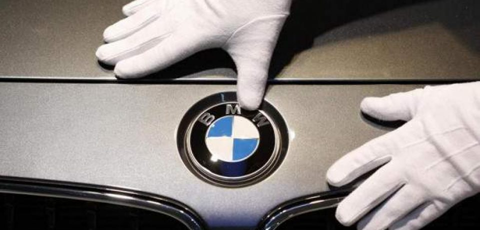 Gambar yang menunjukan tangan yang sedang memegang logo BMW