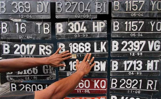 Gambar yang menunjukan pelat nomor kendaraan yang sedang digantung