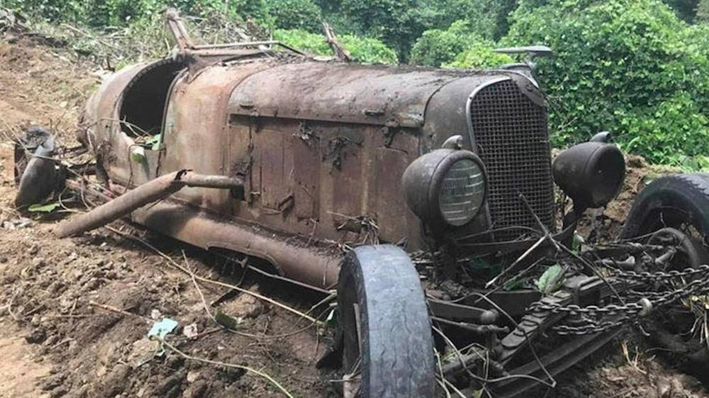 Gambar yang menunjukan mobil klasik yang terkubur di dalam tanah