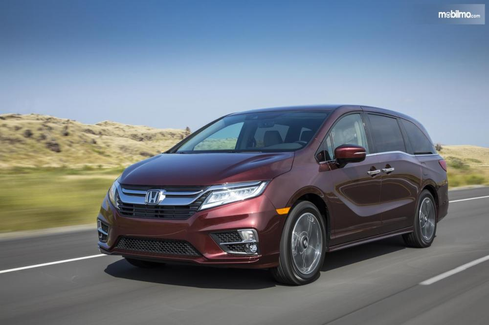 Gambar yang menunjukan mobil baru Honda Odyssey 2019 yang sedang melaju di jalan