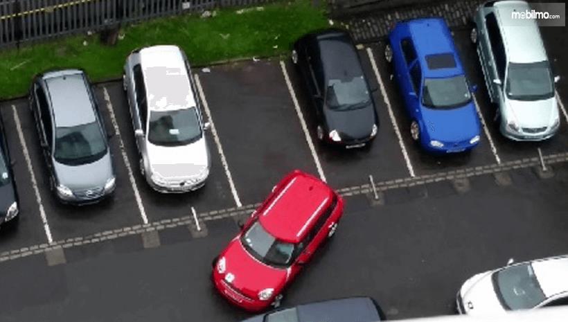 Gambar ini menunjukkan sebuah Mobil warna merah sedang melakukan parkir mundur diantara beberapa Mobil