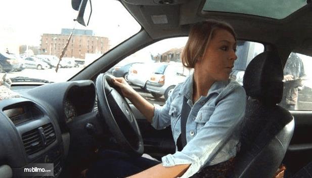 Gambar ini menunjukkan seorang pengemudi wanita sedang menoleh ke belakang