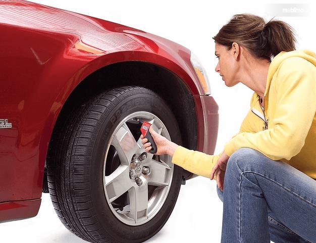 Gambar ini menunjukkan seorang wanita sedang memeriksa tekanan angin ban Mobil