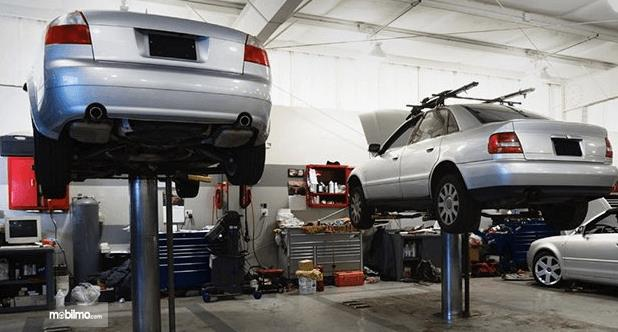 Gambar ini menunjukkan Mobil warna silver sedang diangkat menggunakan alat khusus