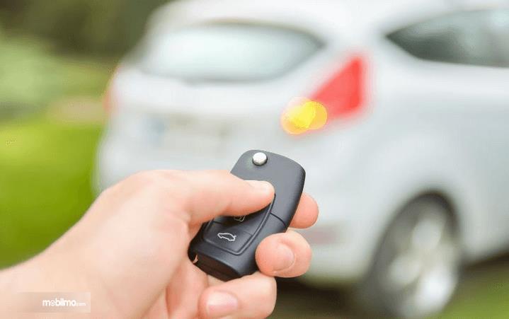 Gambar ini menunjukkan sebuah tangan memegang kunci kendaraan dan terdapat Mobil di depannya terlihat samar