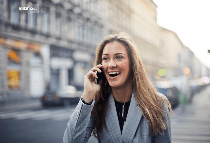 Gambar ini menunjukkan seorang wanita sedang memegang ponsel diletakkan di telinga