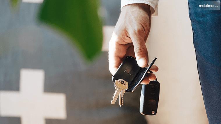 Gambar ini menunjukkan sebuah tangan sedang memegang kunci Mobil