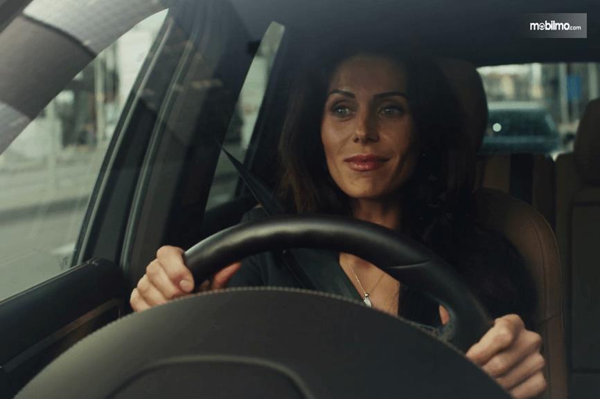 Gambar ini menunjukkan seorang wanita sedang memegang stir dan mengemudi Mobil