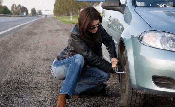 Gambar ini menunjukkan seorang wanita memegang kunci untuk melepas baut pada roda Mobil