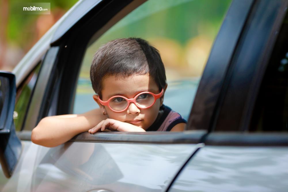 Seorang anak melihat keluar lewat jendela mobil