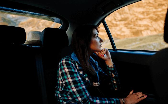 Gambar ini menunjukkan seorang wanita di dalam Mobil sedang melihat keluar melalui jendela Mobilnya