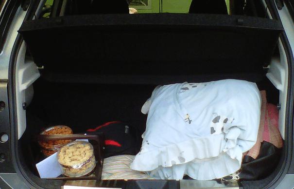Gambar ini menunjukkan beberapa barang sedang diletakkan di dalam bagasi Mobil
