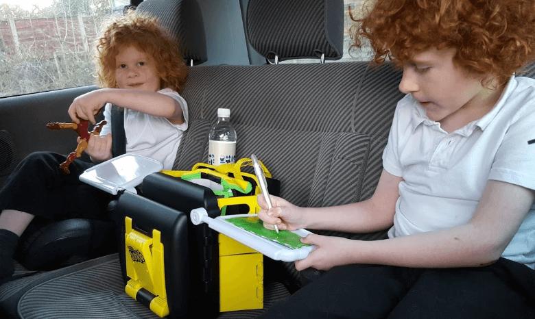 Gambar ini menunjukkan 2 orang anak sedang bermain di dalam Mobil