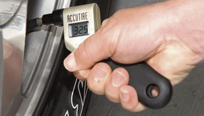 Gambar ini menunjukkan sebuah tangan memegang alat pengukur tekanan angin ban Mobil