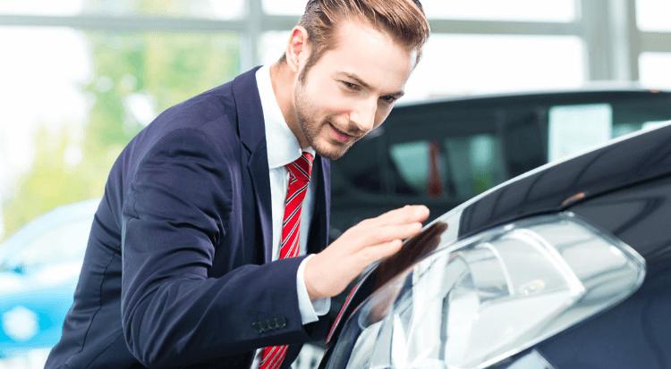 Gambar ini menunjukkan seorang pria sedang memegang bagian bodi pada Mobil