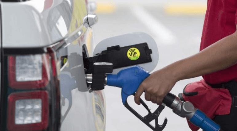 Gambar ini menunjukkan Sebuah tangan sedang memegang alat pengisi bahan bakar warna biru
