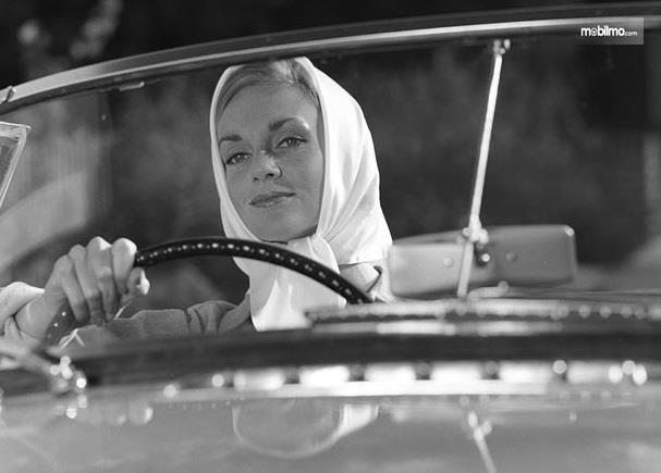 Gambar yang menunjukan pengemudi wanita yang sedang mengendarai obil